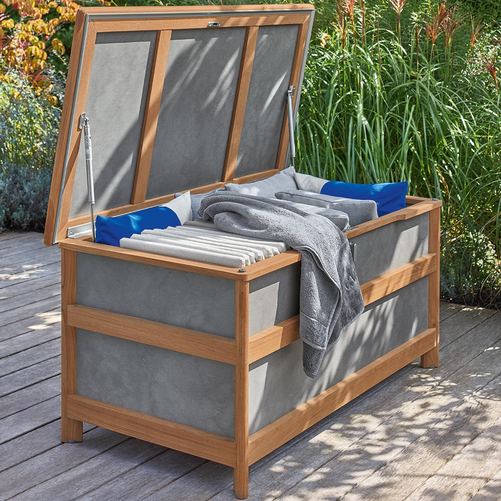 sophisticated cushion chest: the aven medium cushion chest features smooth warm teak and cool synthetic resin panels