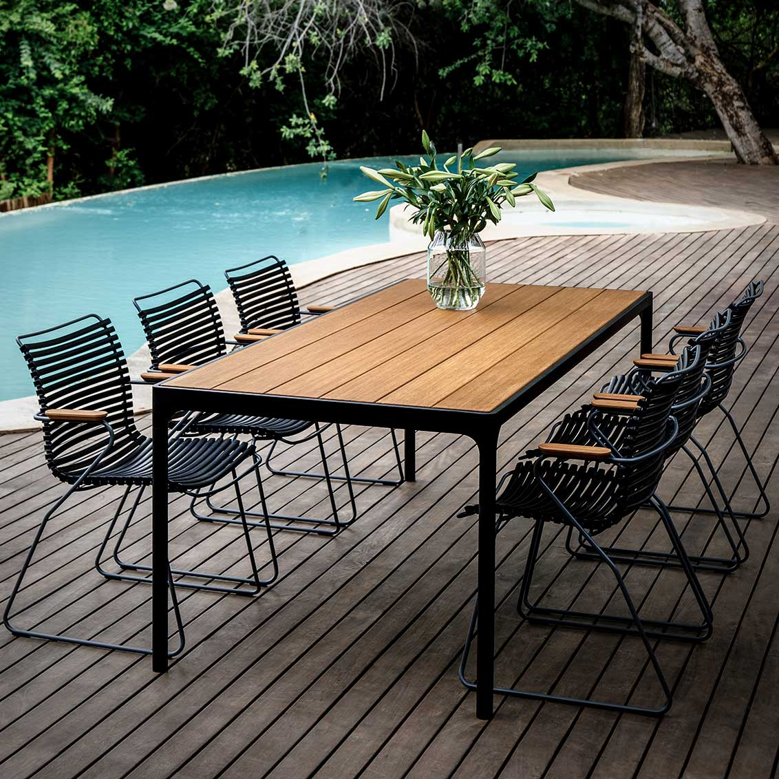 """dinner by the pool: click dining armchairs arranged around the 83"""" four dining table"""
