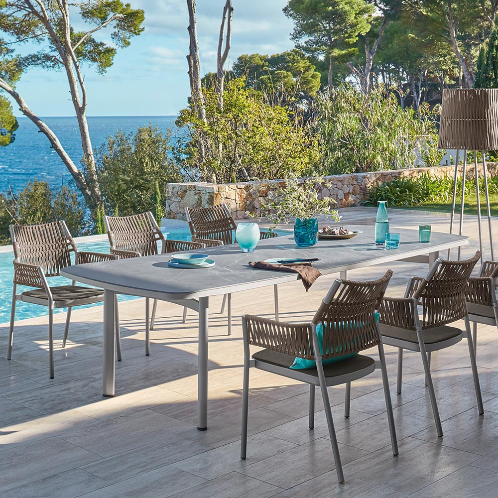 """elegant contours: shifting hues of anodized aluminum frames capture the sun in the 110"""" ceramic dining table and grey-brown armchairs"""