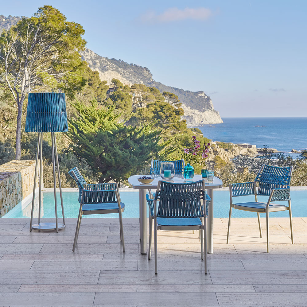 """sea and sky: a 39"""" glass table paired with teal dining armchairs and lamp evoke natural blue hues"""
