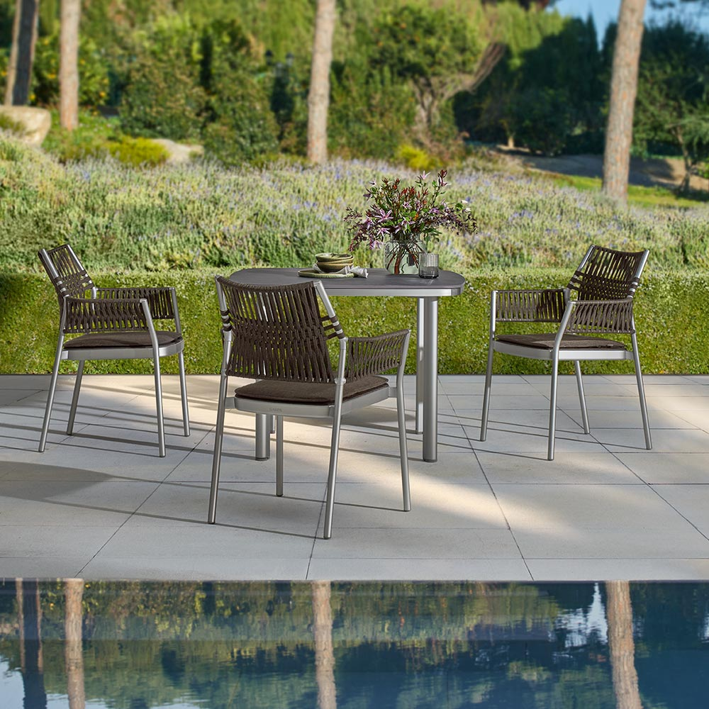 """a natural complement: the grey-brown dining armchairs and 39"""" ceramic dining table pair naturally with the tones of earth, wood, and stone found in most gardens"""