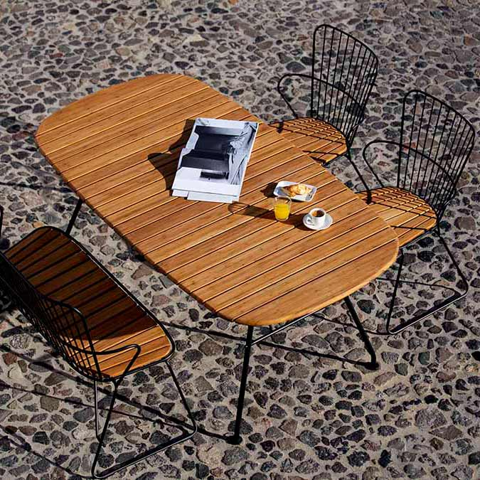 piazza furniture: paon bench and two dining chairs paired with houe's beam dining table