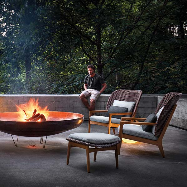 evening ambience: three kay high-back lounge chairs and one ottoman around fire pit | lighting: two ray & one cocoonimage provided courtesy of gloster furniture, inc.