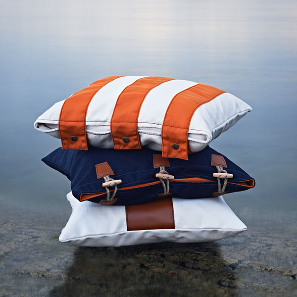 pillow stack (bottom to top): snack (white/ leather logo), hemse (marine blue/ orange insert) and fide (orange-white striped/ copper buttons | sorry fide pillows have been discontinued)