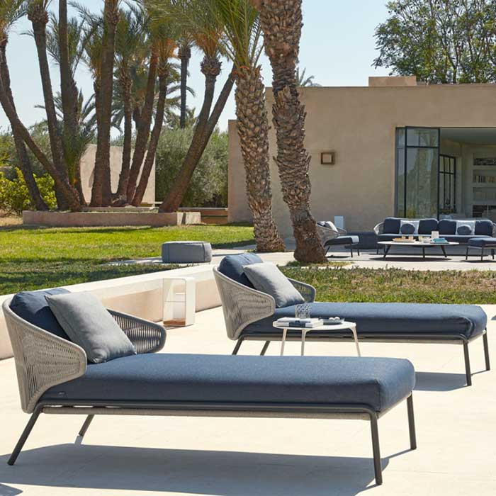 manutti outdoor setting (front to back): two radius chaise lounges, two manutti poufs, and radius 3-seater, 2 1-seaters plus medium footstool
