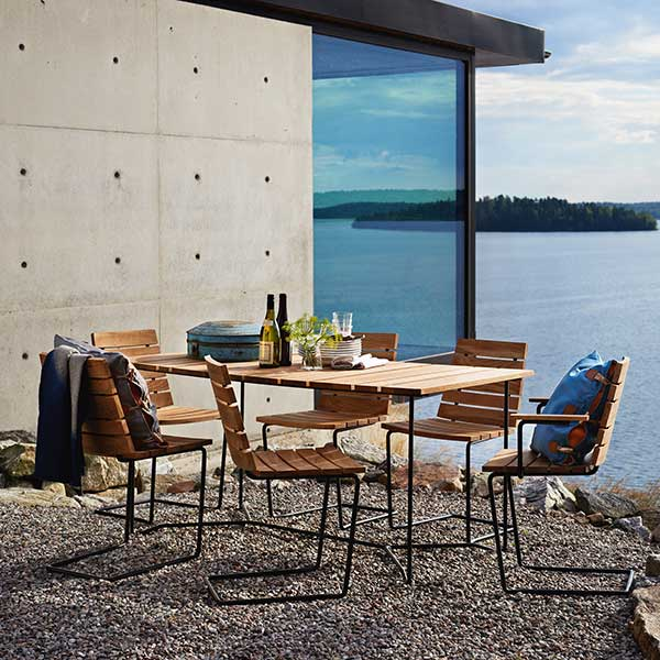 """does well on uneven surfaces: one grinda armchair and five grinda side chairs staged with grinda's 59"""" dining table"""