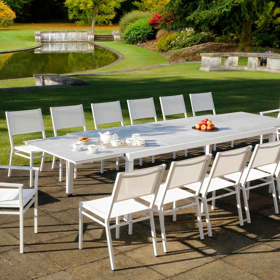 """white elegance: equinox 94-142"""" extending table with ceramic top staged with equinox stacking armchairs and side chairs (sling)"""