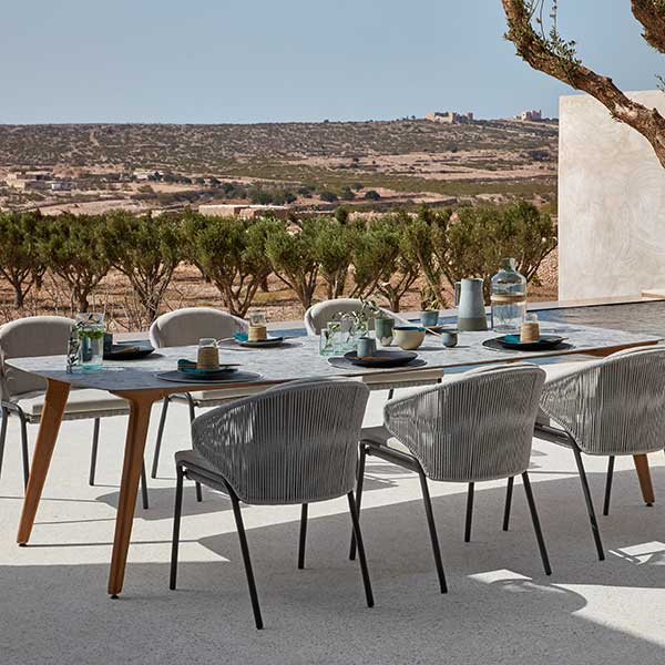 """elegant dining: 104"""" dining table (frame: teak, table top: perla) staged with radius chairs"""