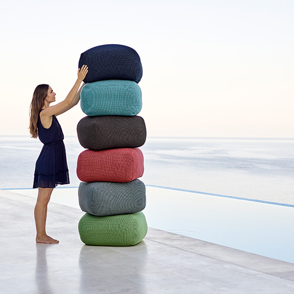 a work of art: divine footstools stacked up (top-bottom: midnight blue, turquoise, brown [discontinued], marsala [discontinued], grey, olive green)
