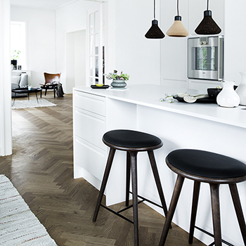 mater's dark-stained oak counter high stools in a residential kitchen setting
