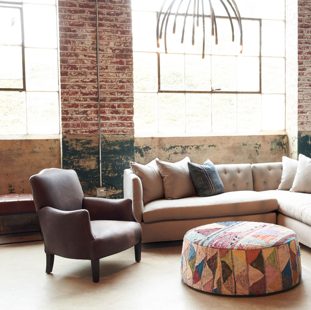 remi leather chair paired in a setting w/ kenso sectional and ottoman