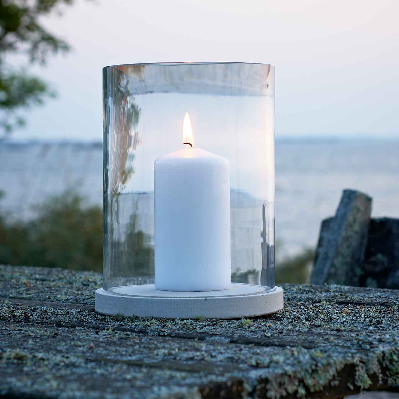 romantic accessory: skargaarden's moja candle lantern in clear glass with concrete plate for stability