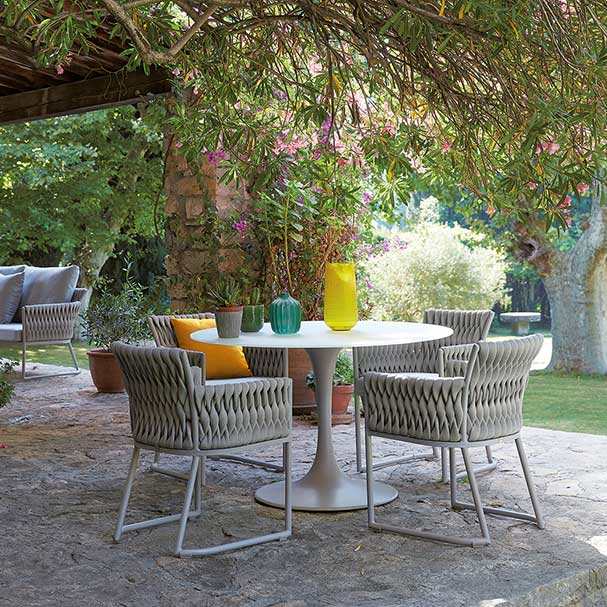 good companions: korol circular dining table in matte gray base and white glass top with four basket dining chairs, all by sifas