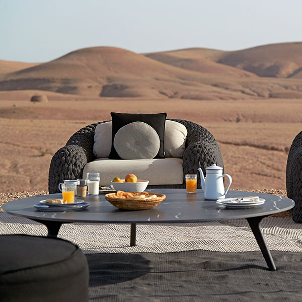 """low lounging: 58"""" coffee table (frame: teak nero, table top: marble black) staged with two kobo 1-seaters"""