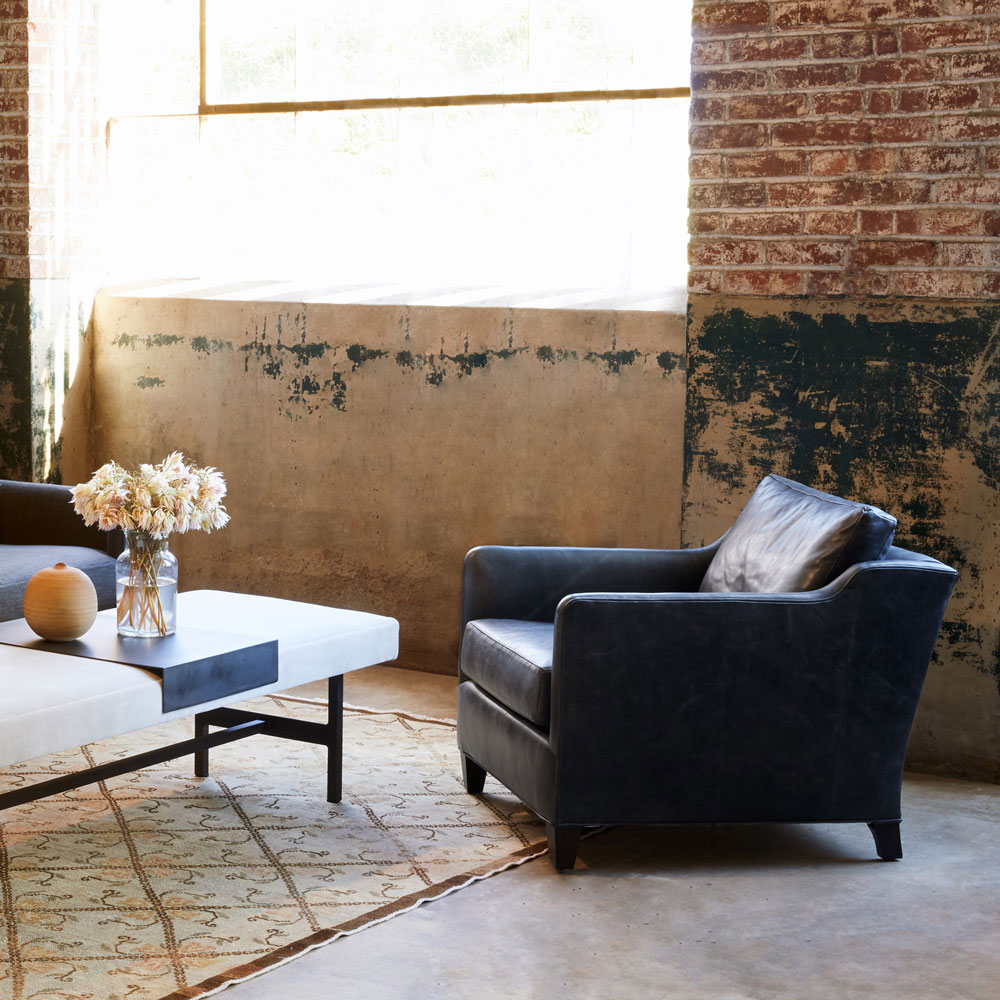 """gunner 96"""" sofa in blake slate, gunner leather chair in pietro granite, styled with harper bench, and eclipse round mirror"""