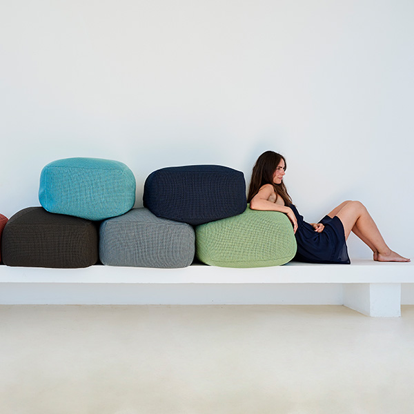 back support: cane-line's footstools are multi-functional (l-r: marsala [discontinued], brown [discontinued], turquoise, grey, midnight blue, olive green)