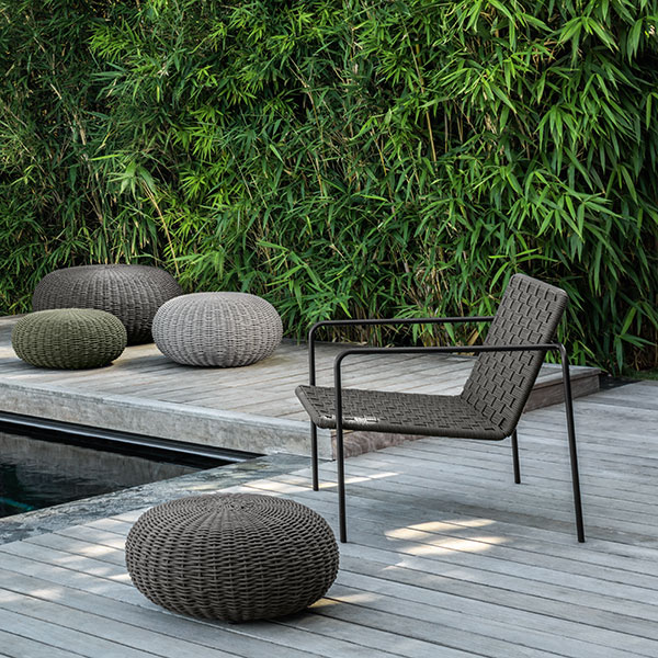 accessorize your outdoor space: talenti's jackie living armchair and poufs in sizes small, medium and big (chair and pouf in foreground in finish graphite/ dark grey)