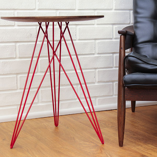 making a mark in any setting: hubbard table in solid walnut with red metal legs