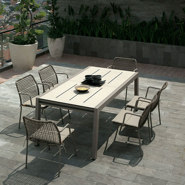 """baia 142"""" powder-coated taupe aluminum extension table (closed) with sandstone HPL top and six manda chairs wovenimage provided courtesy of mamagreen, llc."""