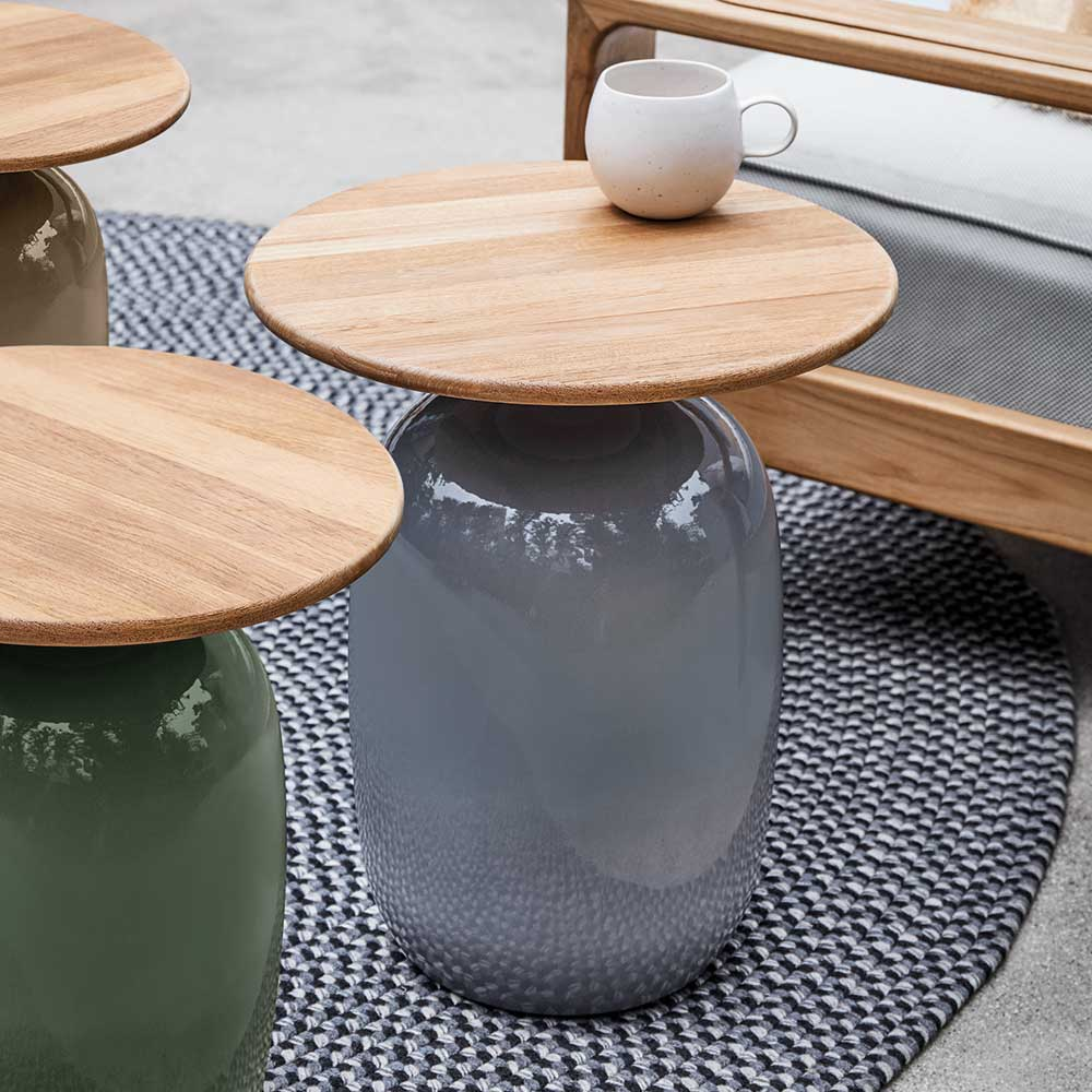 glazed ceramic side tables in coffee, emerald and smoke with natural teak topimage provided courtesy of gloster furniture, inc.