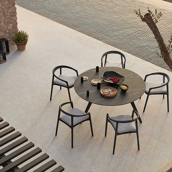 matching the dark roof and window frames: five solid armchairs in teak nero with optional seat cushions around torsa dining table
