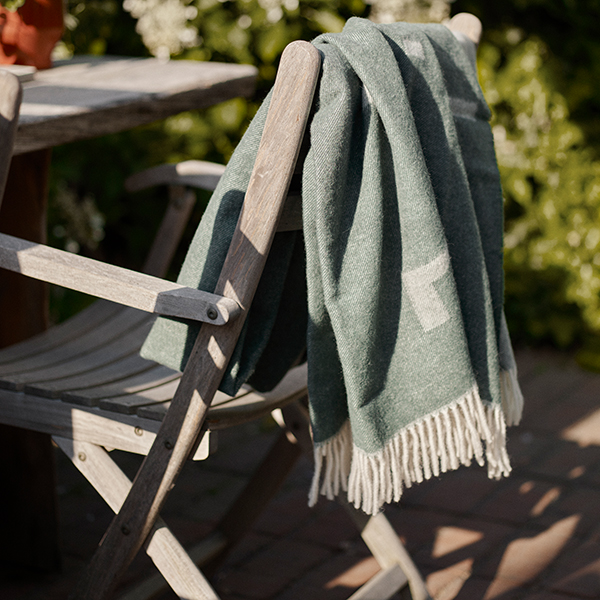 use it outside: iota's luxurious wool blanket in dark green