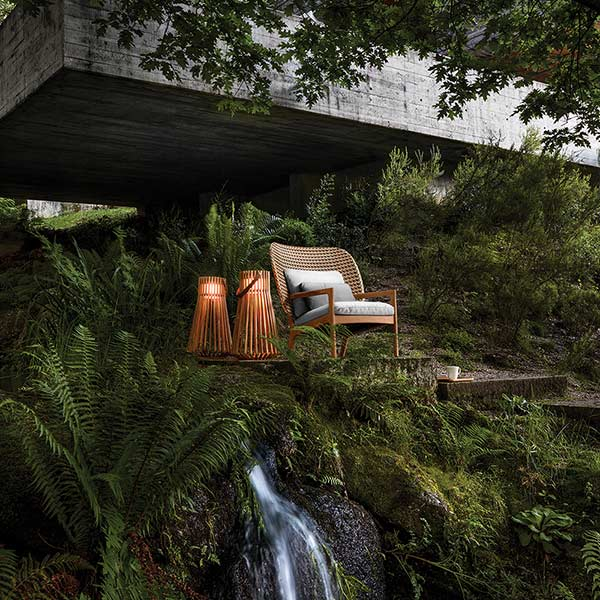 nature retreat: kay high-back lounge chair next to two gloster ray ambient outdoor lightsimage provided courtesy of gloster furniture, inc.