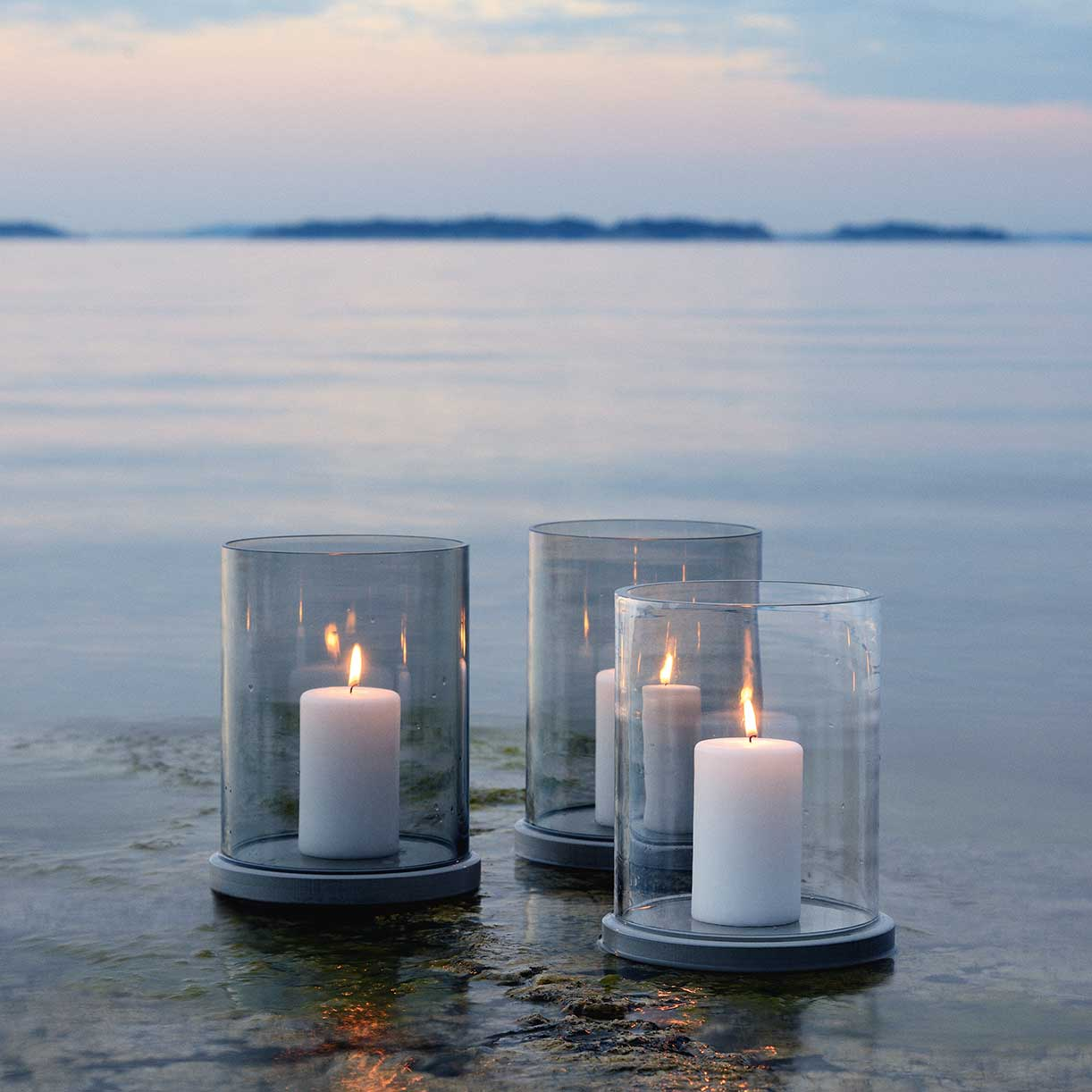 lantern gathering: two moja candle lanterns with grey glass in the background | one moja lantern with clear glass in the foreground