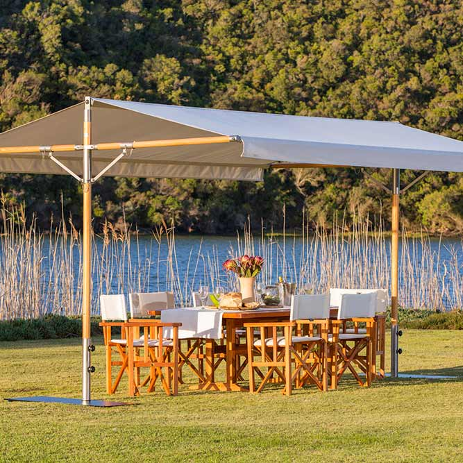 serene setting: papillon dual-pole shade with eucalyptus poles and canopy in sunbrella canvas